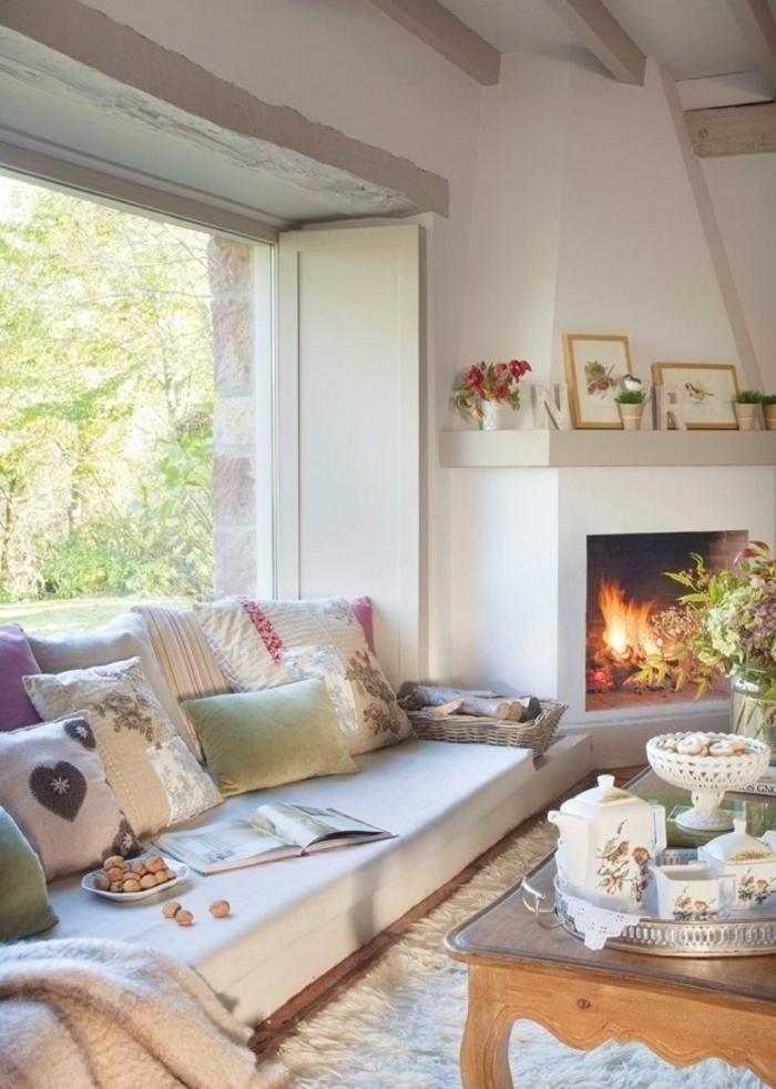 ambiance cocooning, tapis en fausse fourrure, cheminée allumée, grande fenêtre, coussins décoratifs