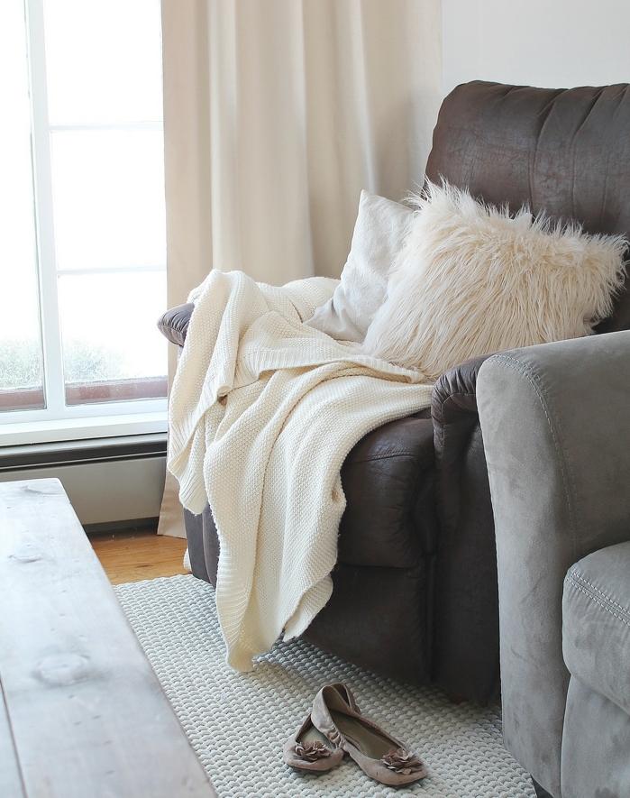 décoration intérieure salon, rideaux longs, fauteuil en cuir, coussins en fausse fourrure, plaid beige
