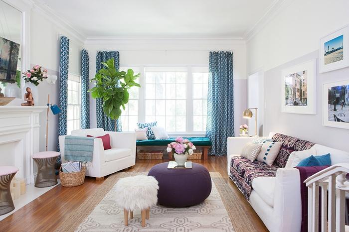 salon cocooning, parquet en bois, rideaux bleus, plantes vertes, fauteuil blanc, pouf, tapis beige