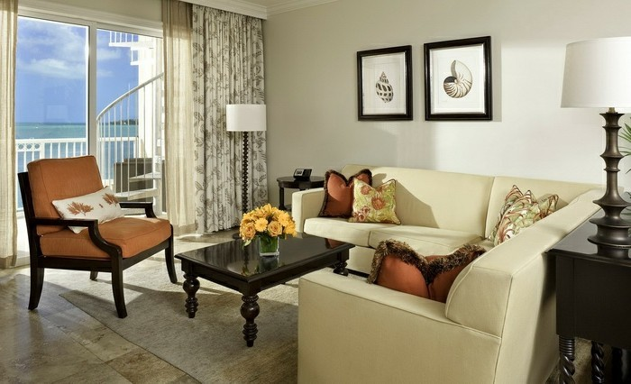 aménager son salon, fauteuil et coussins marron, table noire, grande fenêtre, vue sur la mer
