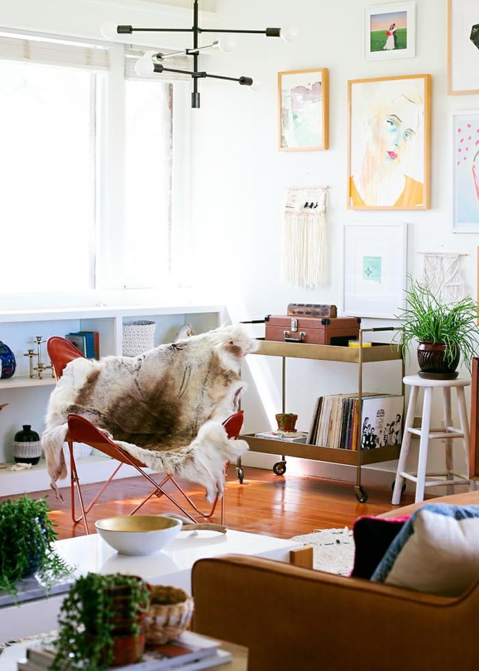 deco sejour, parquet en bois, peintures en cadres orange, plaid en fausse fourrure, canapé marron