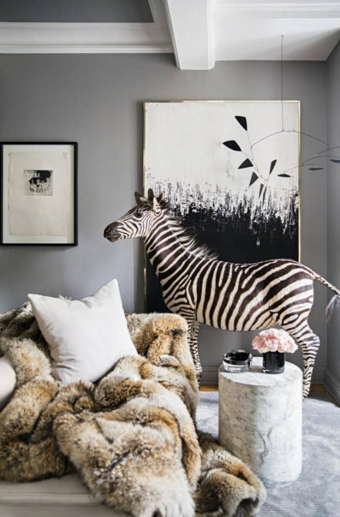 salon cocooning, murs gris, zébre décoratif, plaid en fausse fourrure, coussins décoratifs, tapis gris