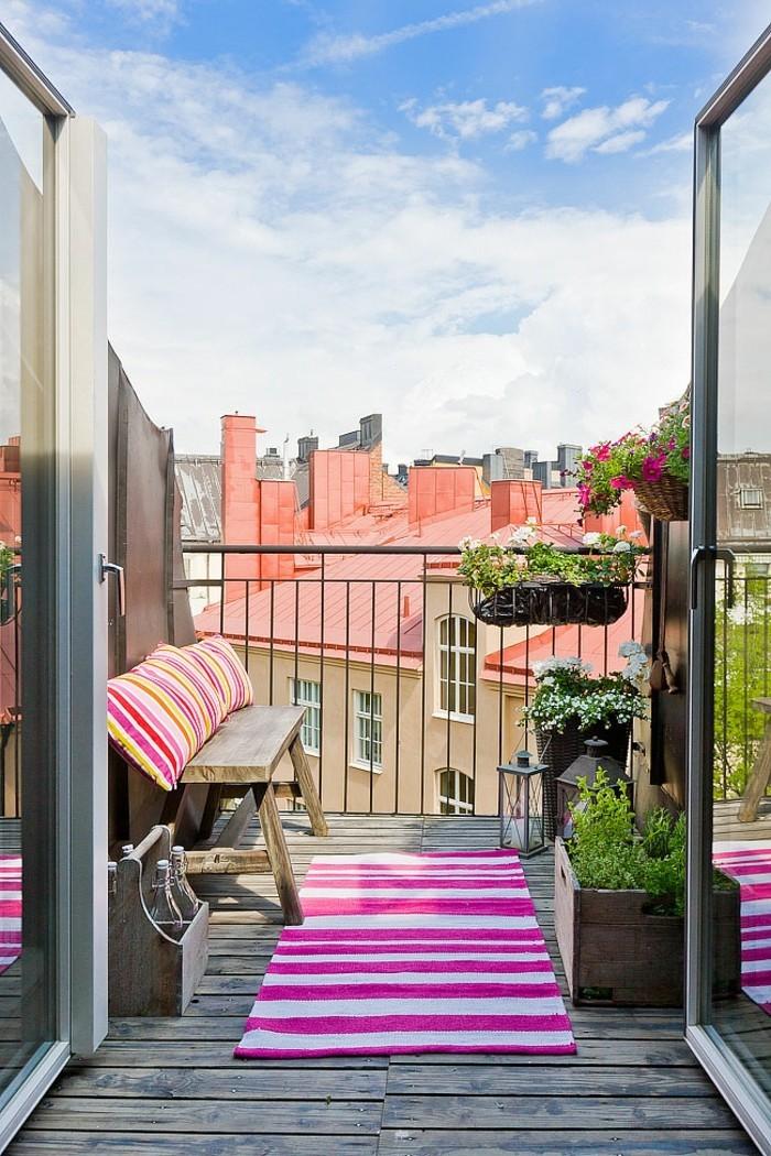 decoration balcon, sol en bois, coussins jaune et rose, belle vue, plantes vertes