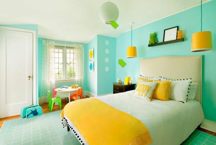 chambre turquoise, couverture de lit jaune, coussins décoratifs, tapis vert, petites chaises