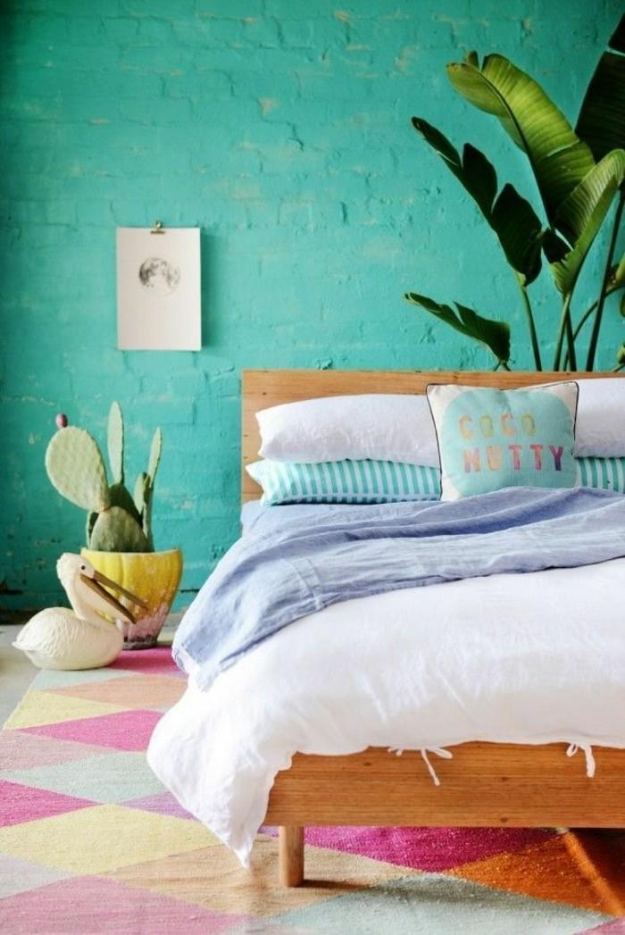 chambre turquoise, plantes tropicales, lit en bois, tapis multicolore, cactus
