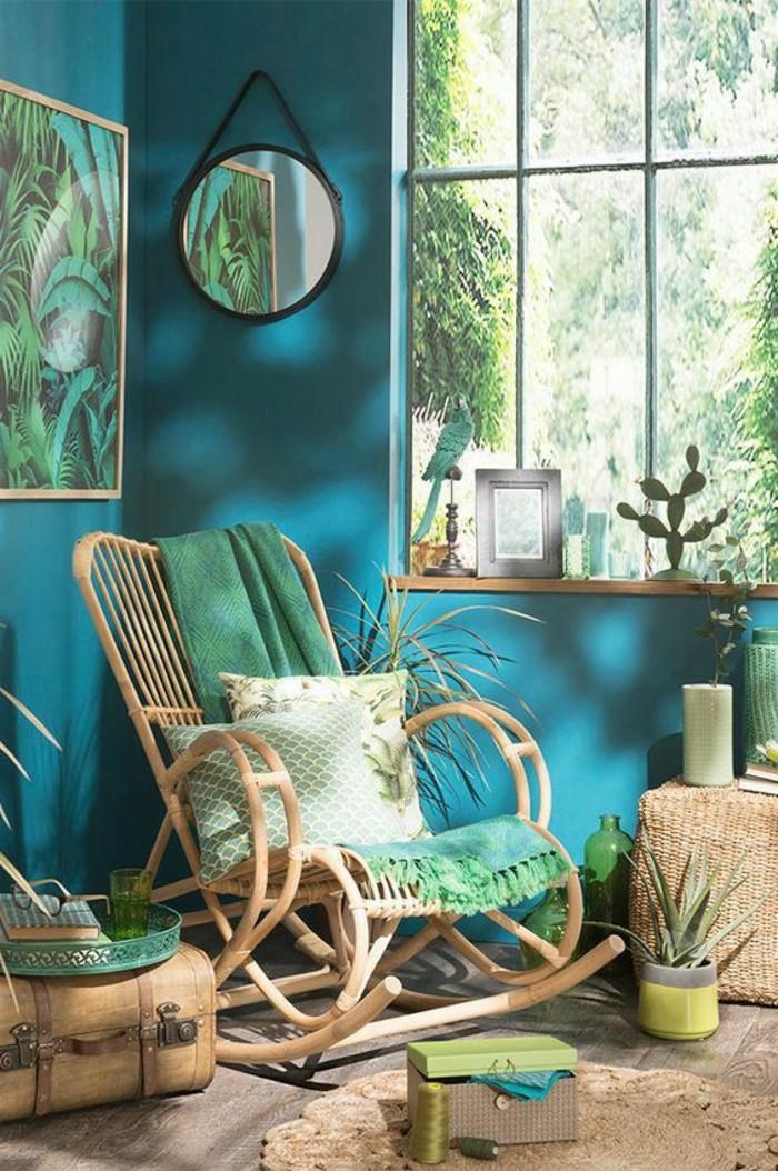 chambre turquoise, miroir rond noir, chaise à basculer, parquet en bois, grande fenêtre, jungle