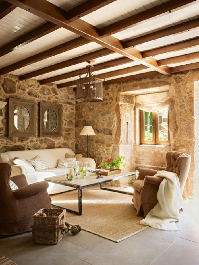 salon cocooning, plafond avec poutres en bois, tapis beige, canapé blanc, miroir rond, fauteuil marron