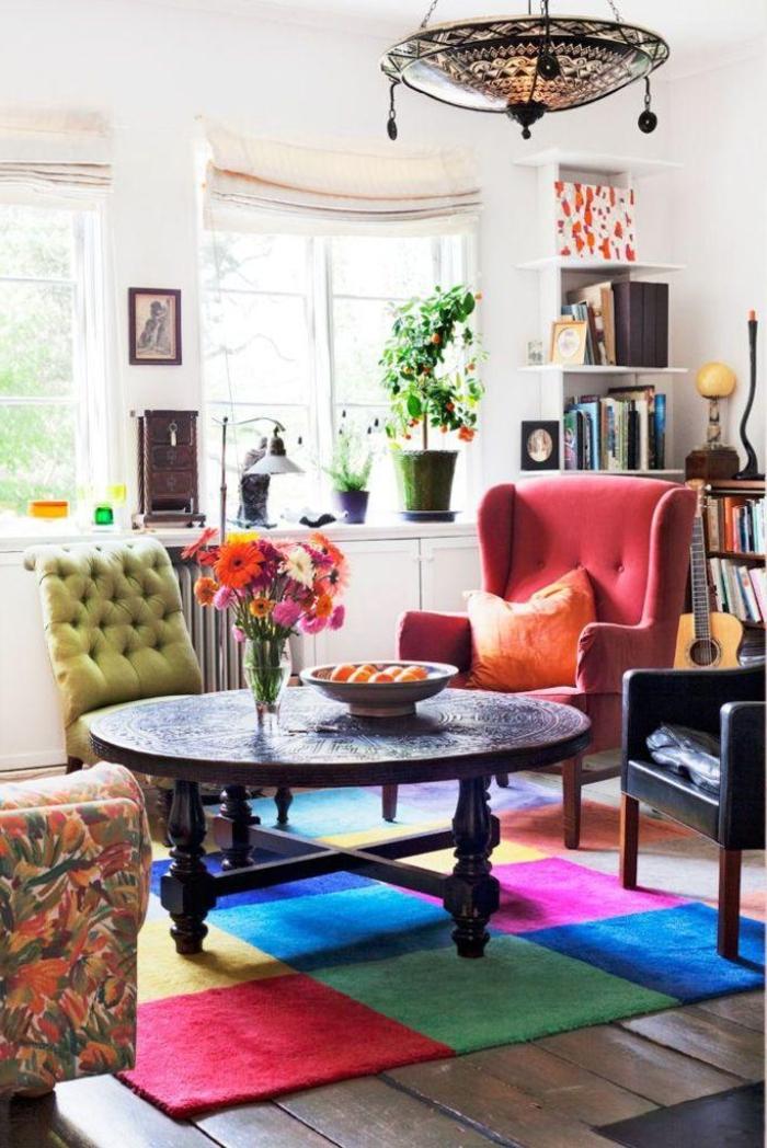 ambiance cocooning, tapis multicolore, fauteuil rose, table ronde en bois, murs blancs