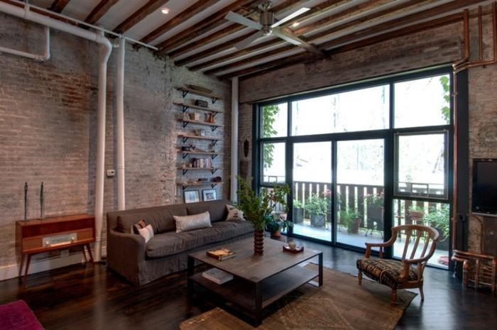 feng shui couleurs, parquet de bois foncé, grande fenêtre, canapé gris, murs en briques