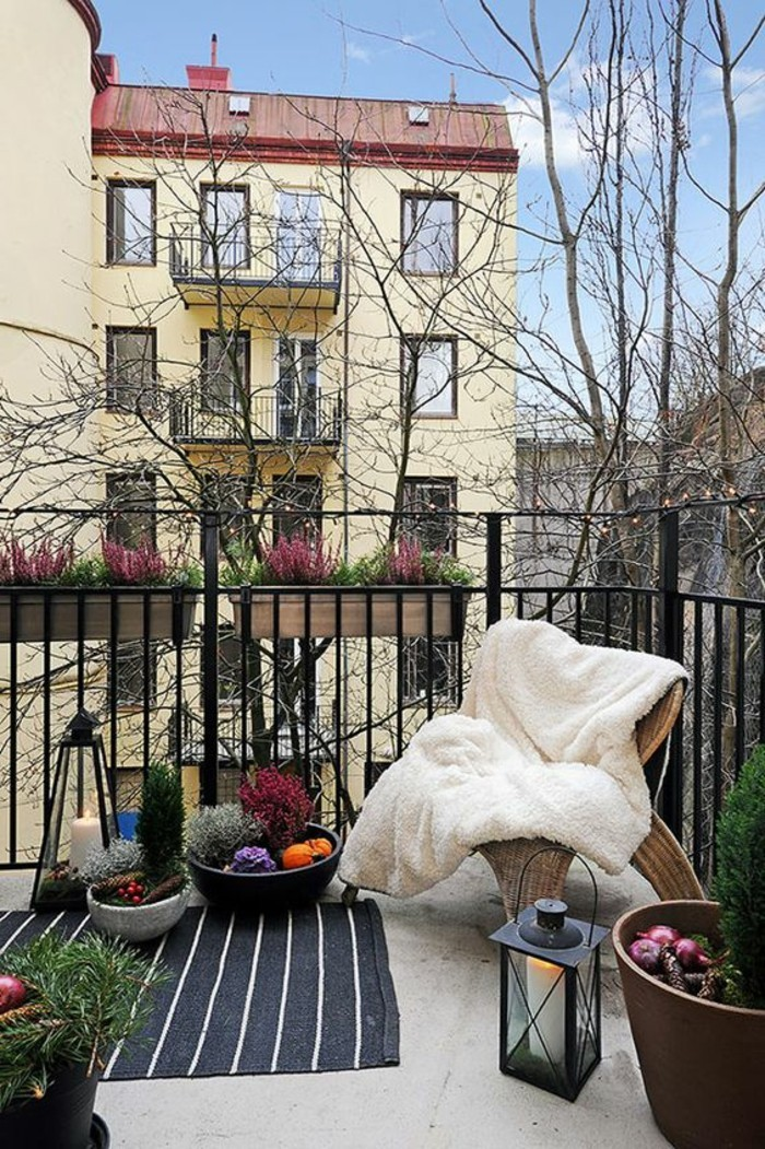 idee deco terrasse, couverture en fausse fourrure, tapis noir et blanc, plantes vertes