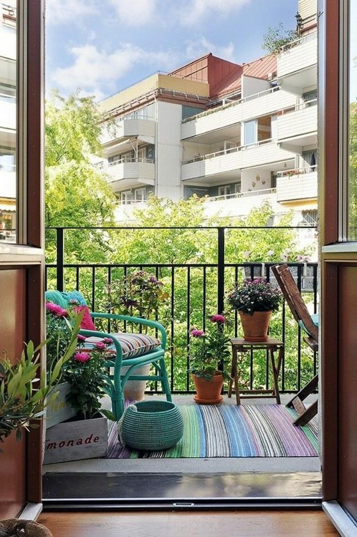 aménager son balcon, chaise turquoise, tapis multicolore, véranda en fer forgé