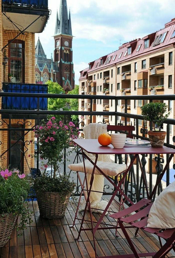 aménagement balcon, belle vue, chaise et table en rouge, tasse de thé, fleurs rose