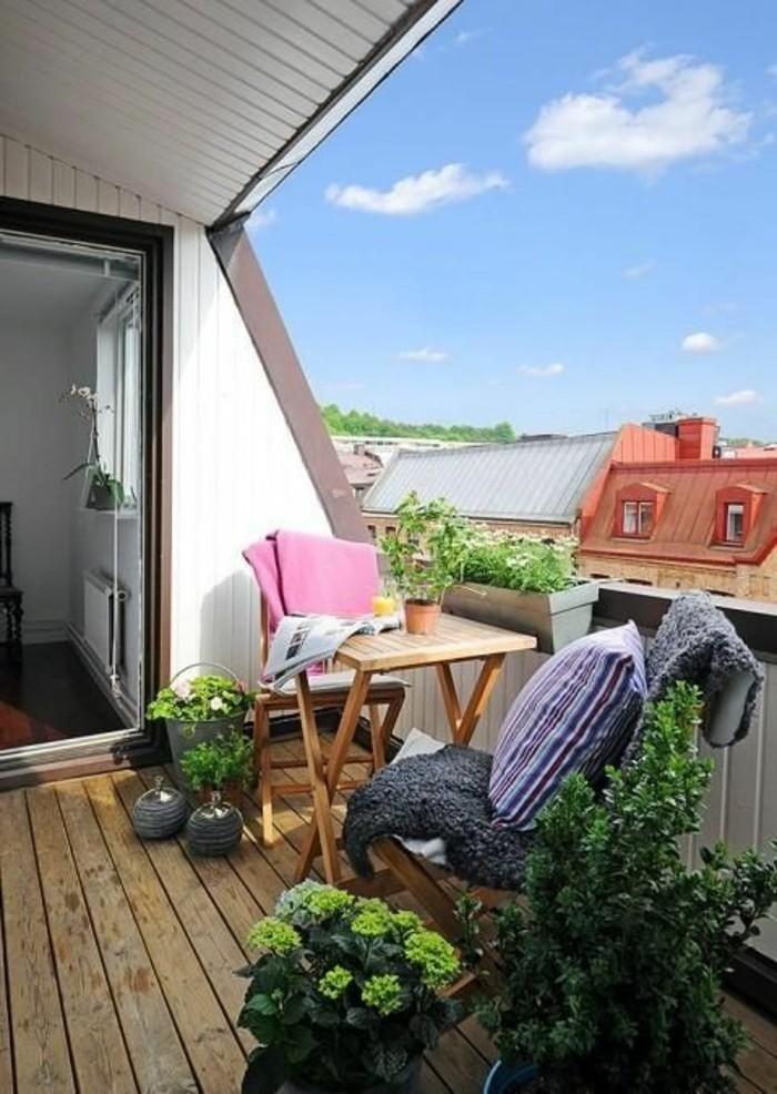 aménager un petit balcon, sol en bois, plantes vertes, table de balcon, coussins décoratifs