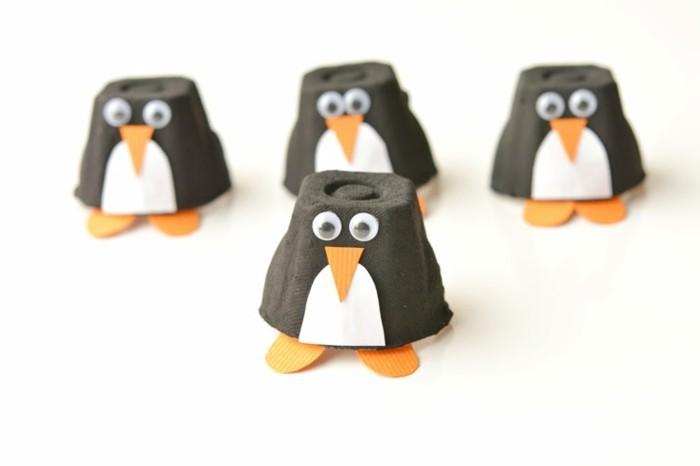 des pingouisne en noir et blanc fabriqués à partir les alvéoles d'une boite à oeufs, nez triangle orange, des pieds