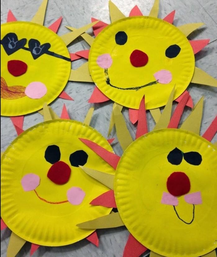 des assiettes en papier repeintes en jaune, avec des traits de visage en tissu, idée activité créative de printemps, soleils jaunes
