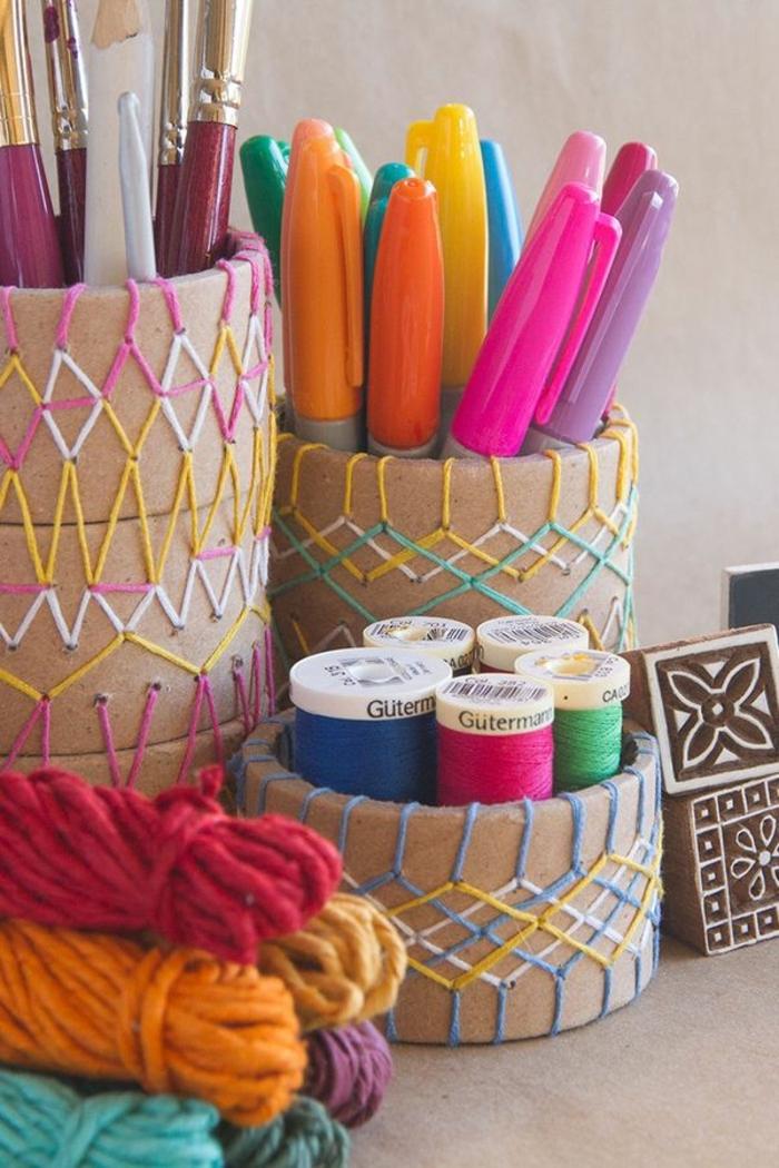 des-bracelets-en-bois-rangés-les-unes-sur-les-autres-pour-former-un-pot-à-crayon-en-bois-et-décorés-de-ficelles-et-remplies-de-feutres-et-pinceaux
