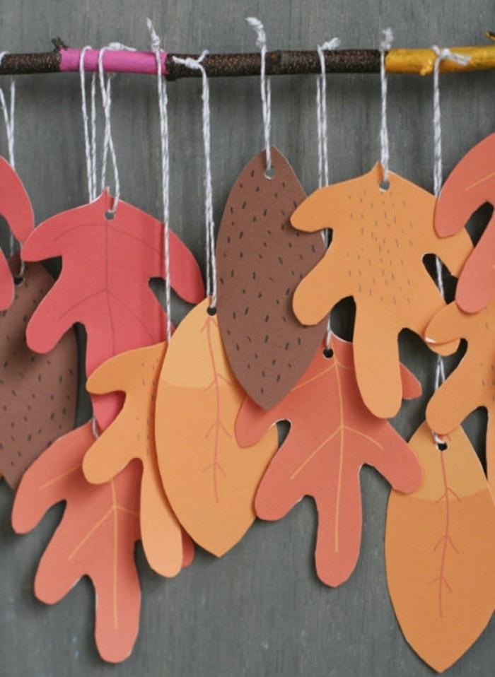 des feuilles mortes en papier orange, rouge, marron, suspendues à une branche, activité manuelle automne maternelle