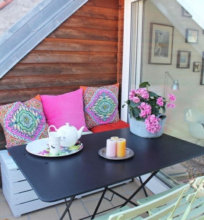 coin repos en plein air, canapé en palette blanc, chaises jardin vert pistache, table noire en métal, carrelage, coussins multicolores, style bohème