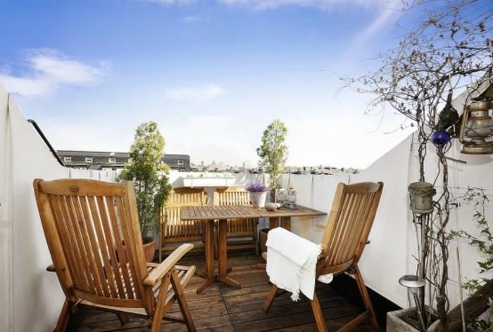 table en bois et chaises pliantes, terrasse tropezienne composite, plantes, idée amenagement petite terrasse