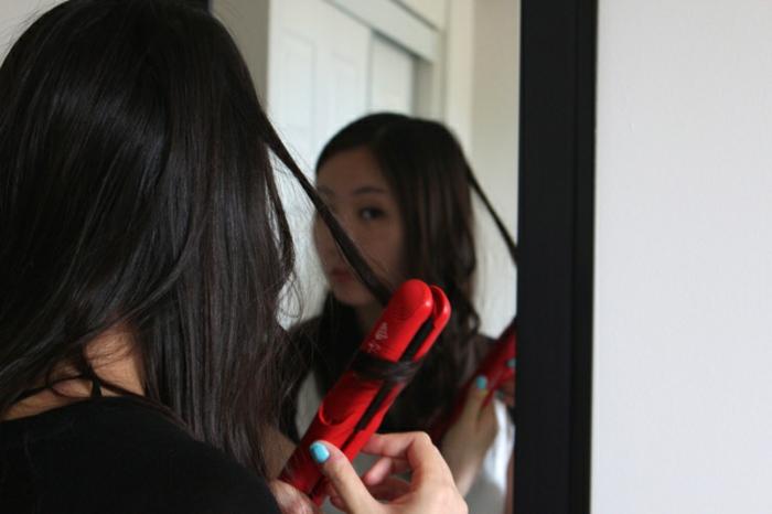faire-des-boucles-avec-un-fer-à-lisser-rouge-cheveux-noirs-manucure-bleue