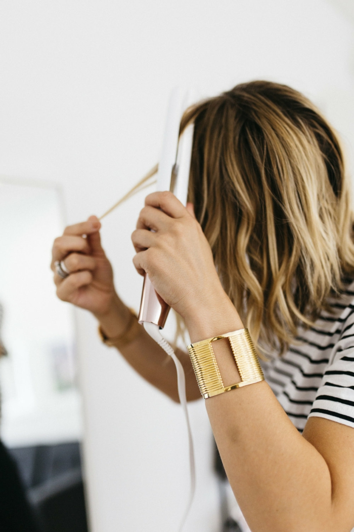 faire-des-boucles-avec-un-fer-à-lisser-t-shirt-blanc-et-noir-bague-cheveux-blonds-et-marron-meches