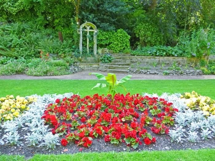une parterre fleuri en longueur, fleurs rouges, jaunes et vertes, sur une pelouse, idée de génie de jardin esthétique