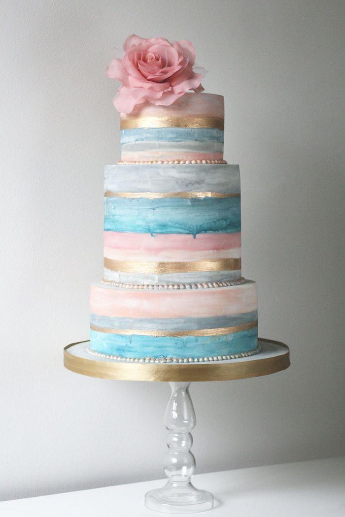 gateau simple et beau de couleur grise, bleu et rose avec des bandes de couleur or et deco de fleur fraiche rose en top