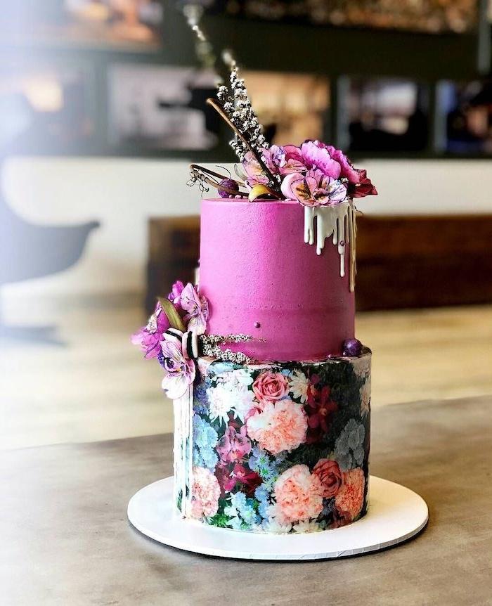 gateau base décorée de motif fleuri sur fond noir et deuxieme couche nappé de creme rose avec decoration fleurie originale