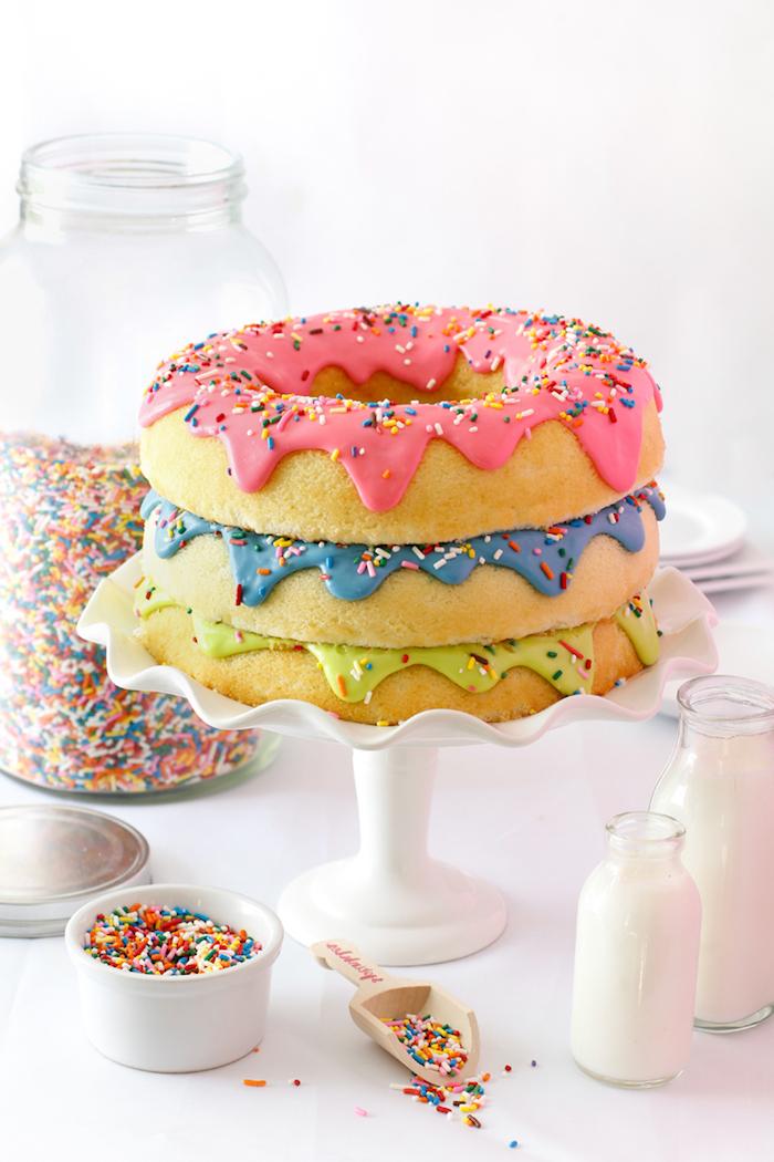 gateau genoise de trois couches décorées de pâte à sucre rose, bleu et vert et des vermicelles colorées