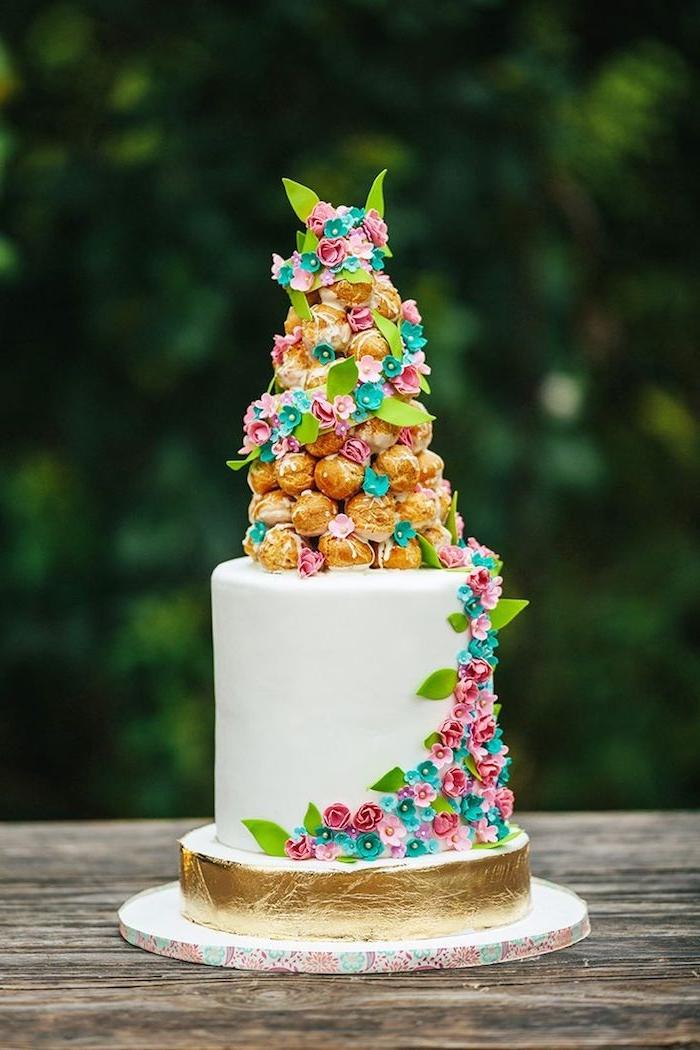gateau décoré de piece montée mariage d'éclaires et de petites fleurs de pate à sucre et base dorée