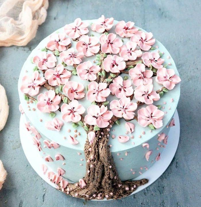 joli gateau original décorée de creme bleu pastel, tronc d arbre en creme au beurre marron et des pétales de fleurs pate à sucre rose