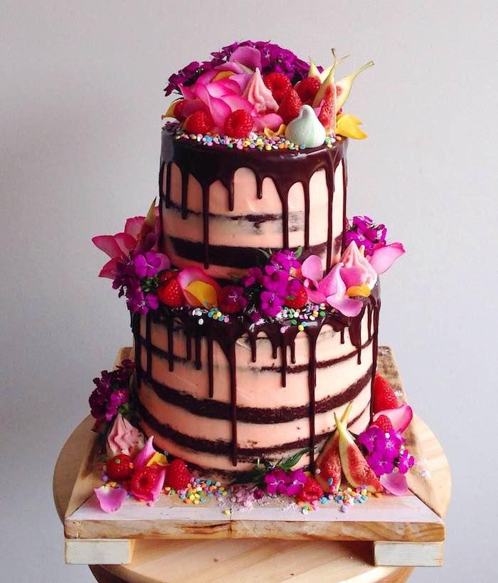 glaçage chocolat pour décorer un gateau au chocolat anniversaire avec creme rose, decoration de fleurs fraiches, billes colorées, meringues et fruits