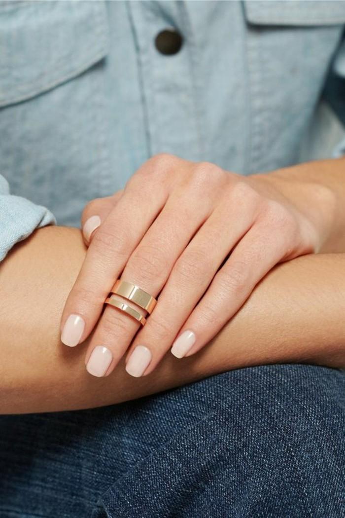 une grosse bague double en or rose portée seule, anneau de phalange élégant