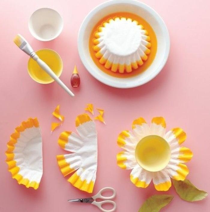 idée-activité-créative-de-printemps-fleur-de-moule-à-muffins-blanche-à-bordure-jaune-avec-un-capuchon-bouteille-au-centre-bricolage-printemps-facile