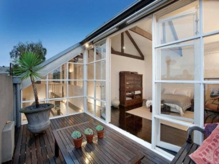 une chambre à coucher ouverte sur une terrase composite, table et chaise en bois, plantes, palmier, idée amenagement terrasse simple