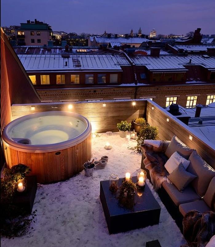 idée comment aménager une terrasse, balnéo, table basse en bois, canapé éclairage romantique, neige, vue urbaine