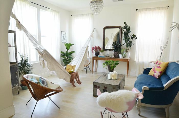 coussin cocooning, hamac blanc, canapé bleu, chaise ronde en paille, grandes fenêtres, miroir marron