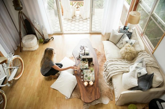 canapé cocooning, parquet en bois, vélo, table en bois, tapis en fausse fourrure