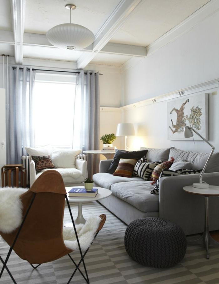coussin cocooning, fauteuil marron, pouf gris, rideaux longs, murs blancs, plantes vertes