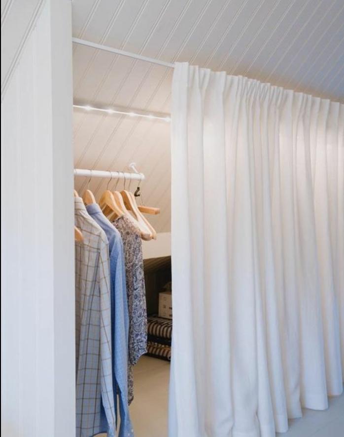 idée de meuble sous pente, dressing avec rideau blanc, penderie pour suspendre robes, chemises, manteaux, éclairage LED