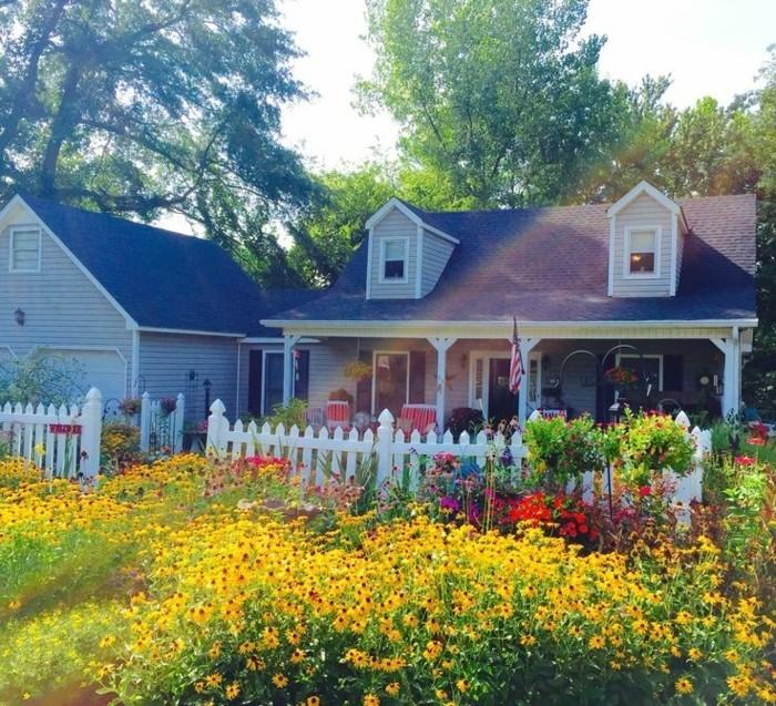 exemple, modèle de jardin à l'anglaise, fleurs jaunes et autres couleurs, parterre de fleur aménagé près d'une palissade blanche, maison rustique