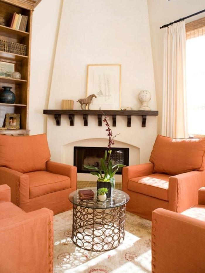 ambiance cocooning, fauteuil orange, table ronde en verre ,tapis blanc, bibliothèque en bois