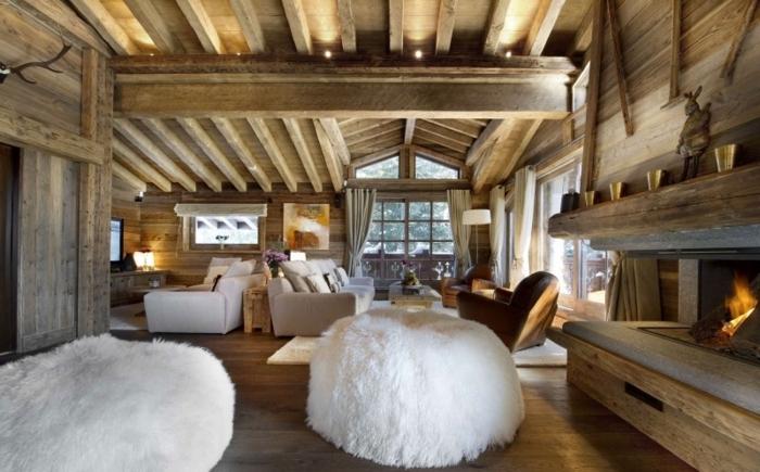 canapé cocooning, plafond avec poutres en bois, grand pouf blanc, cheminée allumée, grandes fenêtres