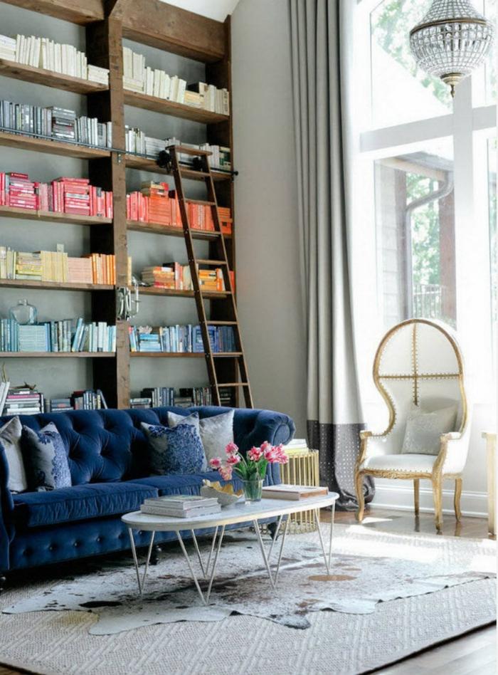 ambiance cocooning, canapé bleu foncé, bibliothèque en bois, rideaux longs, tapis beige