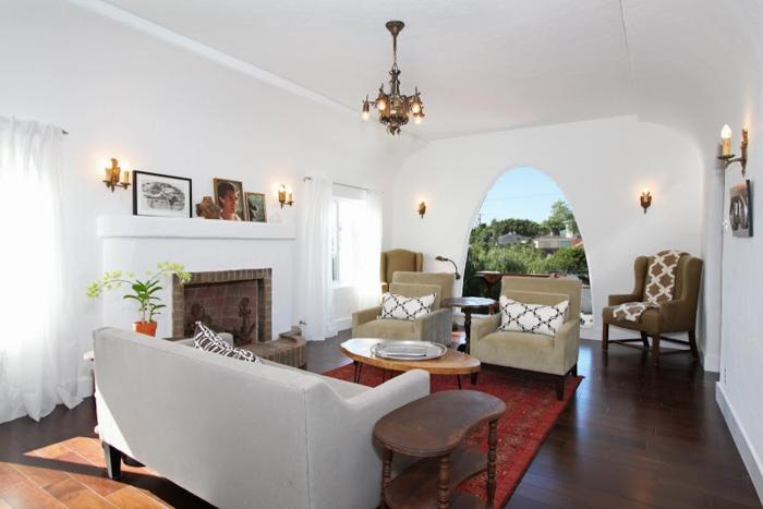 salon cocooning, murs blancs, rideaux longs, fauteuils beige, tapis rouge, cheminée en brique