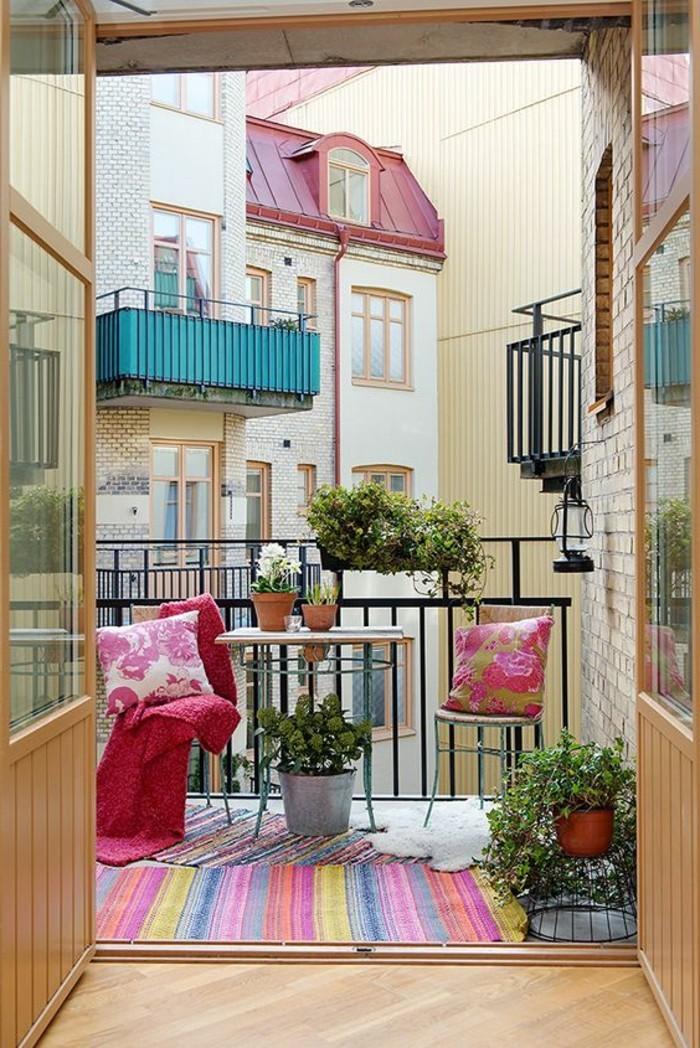 aménager un petit balcon, tapis multicolore, couverture rose, coussins à fleurs, table en bois