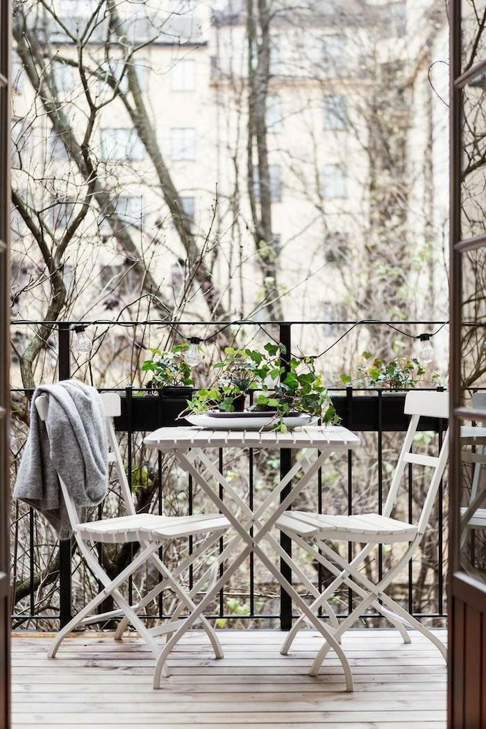 aménager son balcon, sol en bois, véranda en fer forgé, fleurs vertes, chaise blanche, gilet gris