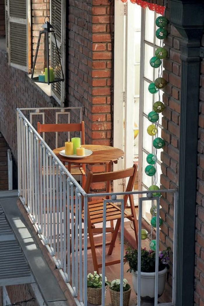 aménager son balcon, table ronde de balcon, chaise en bois, bougies vert et jaune, guirlande lumineuse
