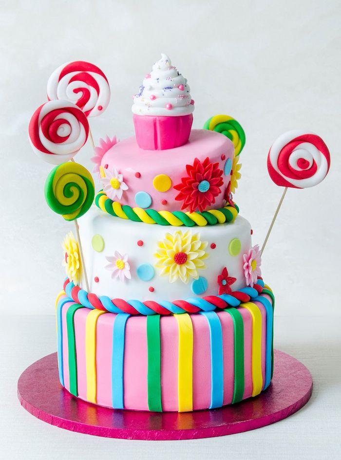realiser un gateau anniversaire adulte décoré de p6ate à sucre de couleurs variées avec cupcakes en top et sucette de sucre