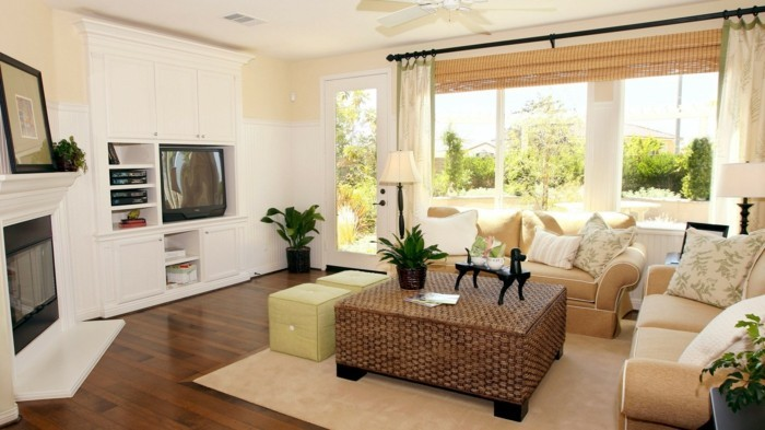 aménager son salon, canapé beige, rideaux longs, plantes vertes, bibliothèque blanche